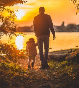 A man and a child walking towards the sun.